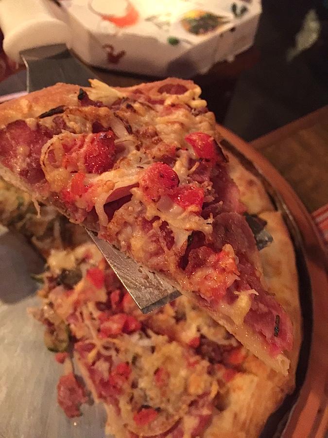 Pizza da casa leva três tipos de linguiça, tomatinho, cebola e é gratinada com parmesão. Uma delícia
