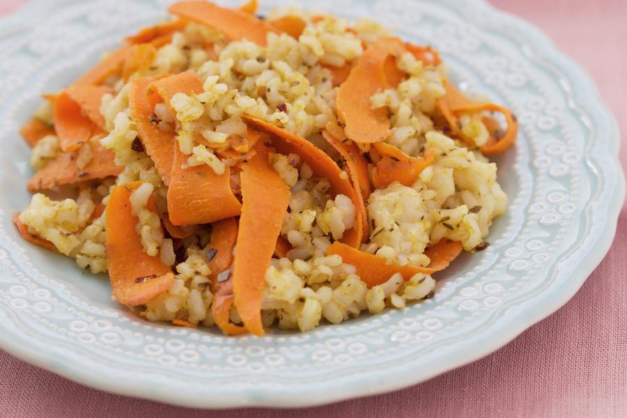 Arroz Integral com Cenoura e Curry Lamine uma cenoura com a ajuda do descascador de legumes ou rale. Em uma frigideira aqueça uma colher de chá de curry com uma colher de sopa de azeite. Coloque a cenoura e deixe fritar um pouco. Depois misture o arroz e ajuste o sal.